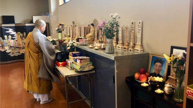 Sư cô Thích Tâm Trí thắp hương trên ban thờ đặt nhiều bài vị của các thực tập sinh và du học sinh Việt.