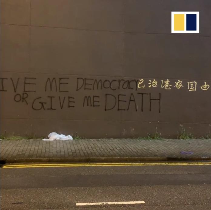 Thông đệp Dân Chủ Hay Là Chết được người biểu tình vẽ trên nền tường thành phố.