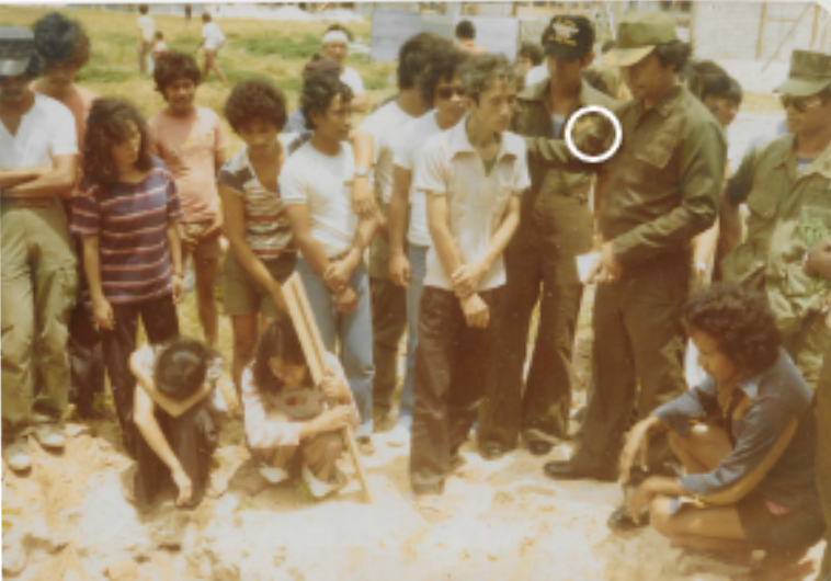 Thiếu tá ngưởi Phi luật Tân chì huy trưởng  đảo Pag Asa  phân ưu trong đám ma đứa con hai tuổi của tôi chết khát trên thuyền trước khi thuyền tới đảo (mùa bão Vu Lan năm 1978).  Hai người đàn bà ngồi gục đầu là vơ tôi và em gái tôi. Người chụp ảnh: môt quân nhân Phi luật Tân ở Pag Asa.