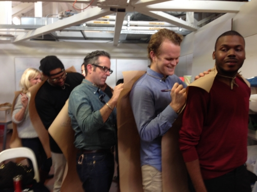 Stanford d.fellows, Susan Dix-Lyons, Jason Mayden, David Clifford, Tim Shriver and Michael Tubbs writing appreciations on each other's superhero capes.
