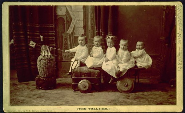 Five Small Children Seated on Vehicle with the Child in the Front Holding a Small US Flag | Circa 1891