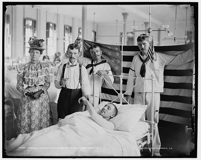 Taking a Patient's Pulse at the Brooklyn Navy Yard Hospital with Flag in the Background | 1890