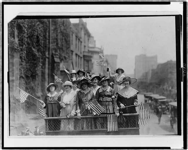 Group of Women Standing on Top of Vehicle Waving Flags in New York City | Circa 1907