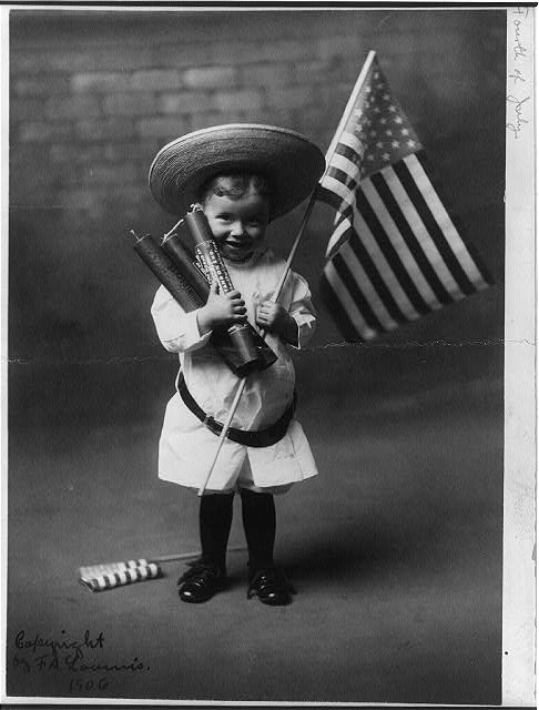 Little Boy Holding Three Large Firecrackers and an American Flag | Circa 1906