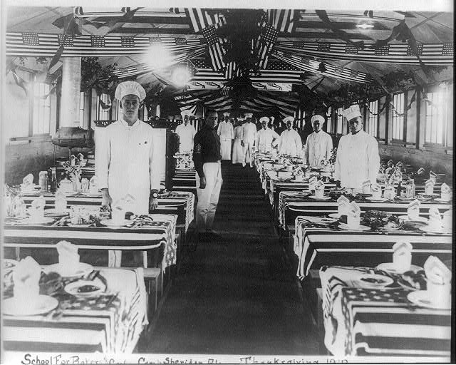 School for Bakers and Cooks, Camp Sheridan, Alabama with Tables and Ceiling Decorated with Flags | Circa 1918