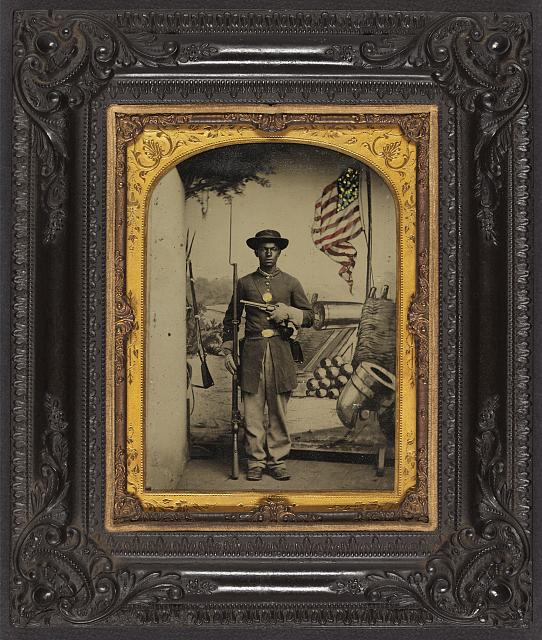 African American Soldier in Union Uniform with a Rifle and Revolver in Front Painted Backdrop Showing Weapons and American Flag at Benton Barracks, Saint Louis, Missouri | Circa 1863-1865