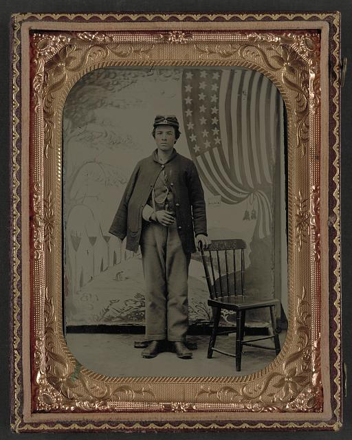 Soldier in Uniform with Arm in Sling in Front of Painted Backdrop Showing Military Camp and American Flag | Circa 1861-1865