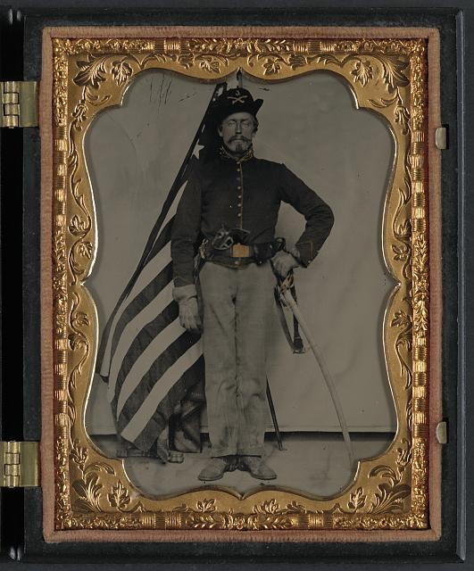 Soldier in Union Cavalry Uniform with Colt Dragon Revolver and Sword in Front of American Flag | Circa 1861-1865