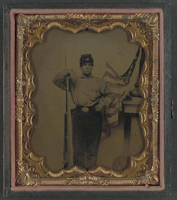 Soldier in Union Uniform with Bayoneted Musket in Front of Painted Backdrop Showing American Flag and Column Pedestal | Circa 1861-1865