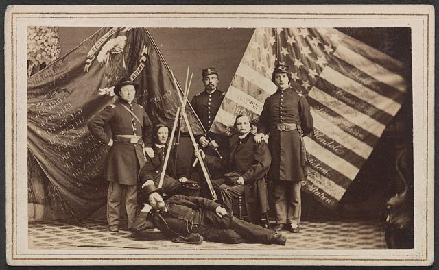 Soldiers of 63rd New York Infantry Regiment in Uniform and One Man in Civilian Dress with Federal and State Battle Flags and Rifle Stack | Circa 1861-1865