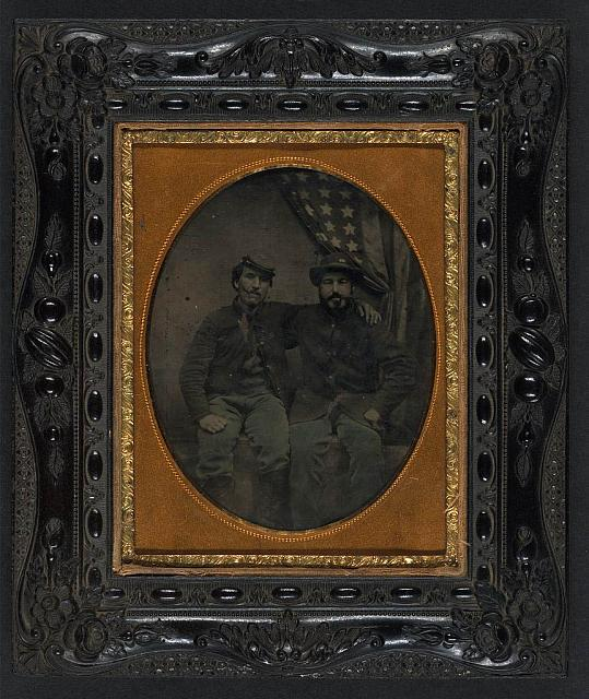 Two Soldiers in Union Uniform with Cigars in Mouths in Front of American Flag, One Being in a 6th Army of the Potomac Forage Hat | Circa 1861-1865