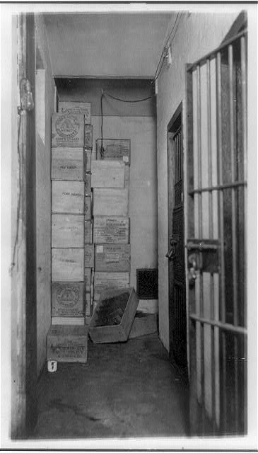 Cases of Confiscated Liquor Stacked in Corner of Room with Barred Doors   Circa 1921
