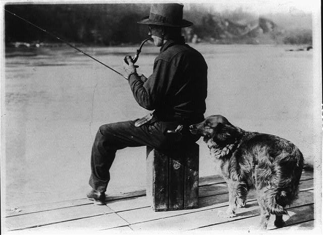 Hooch Hound, a Dog Trained to Detect Liquor, Sniffs at the Flask in the Back Pocket of a Man, Fishing on a Pier on the Potomac River   Circa 1922