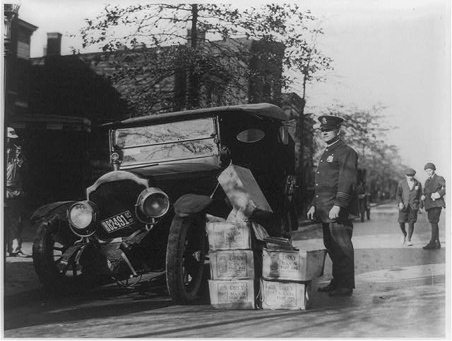 Policeman Standing Alongside Wrecked Car and Cases of Moonshine   Circa 1922