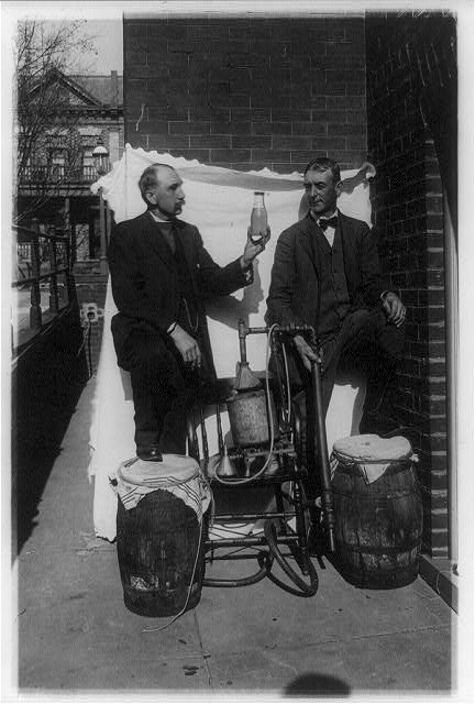 Two Men Standing Outdoors with Small Still, One of Them Holding Up a Bottle of Liquor   Circa 1921