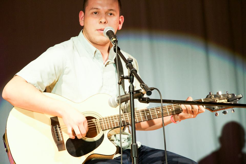 Brother Mario Alberto playing his guitar at a CU event.