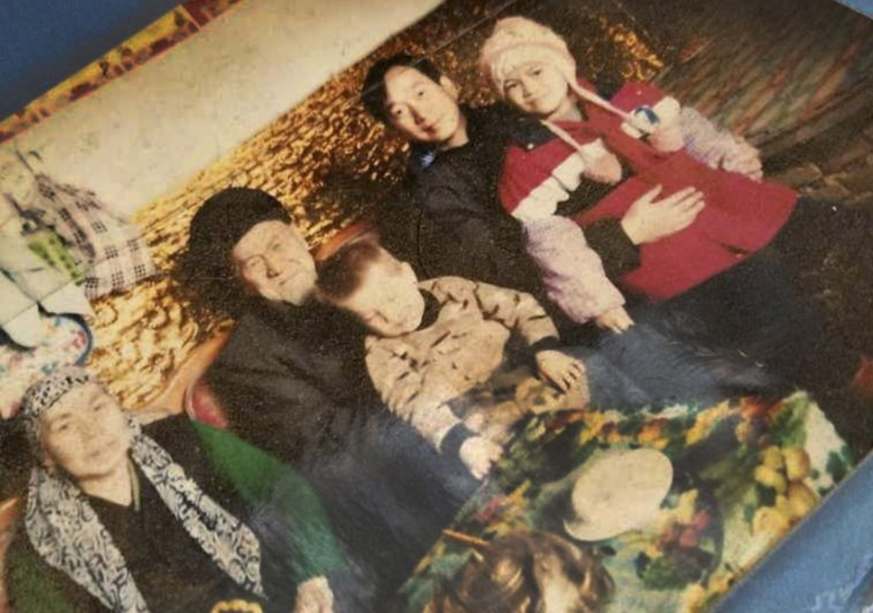 The younger man on the right side of this photo is a government employee who is being housed with this Uighur family.