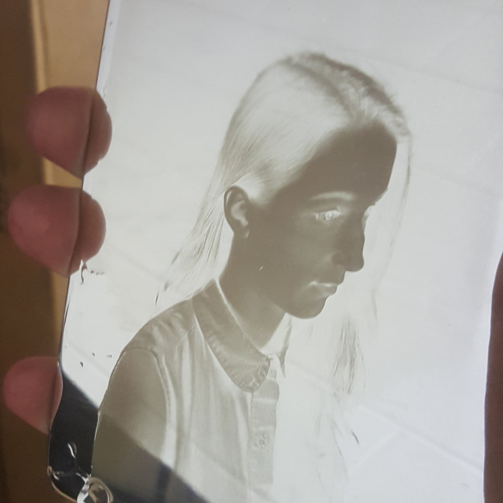 A daguerreotype's mirror surface reflecting on a white wall, which shows a Negative image.