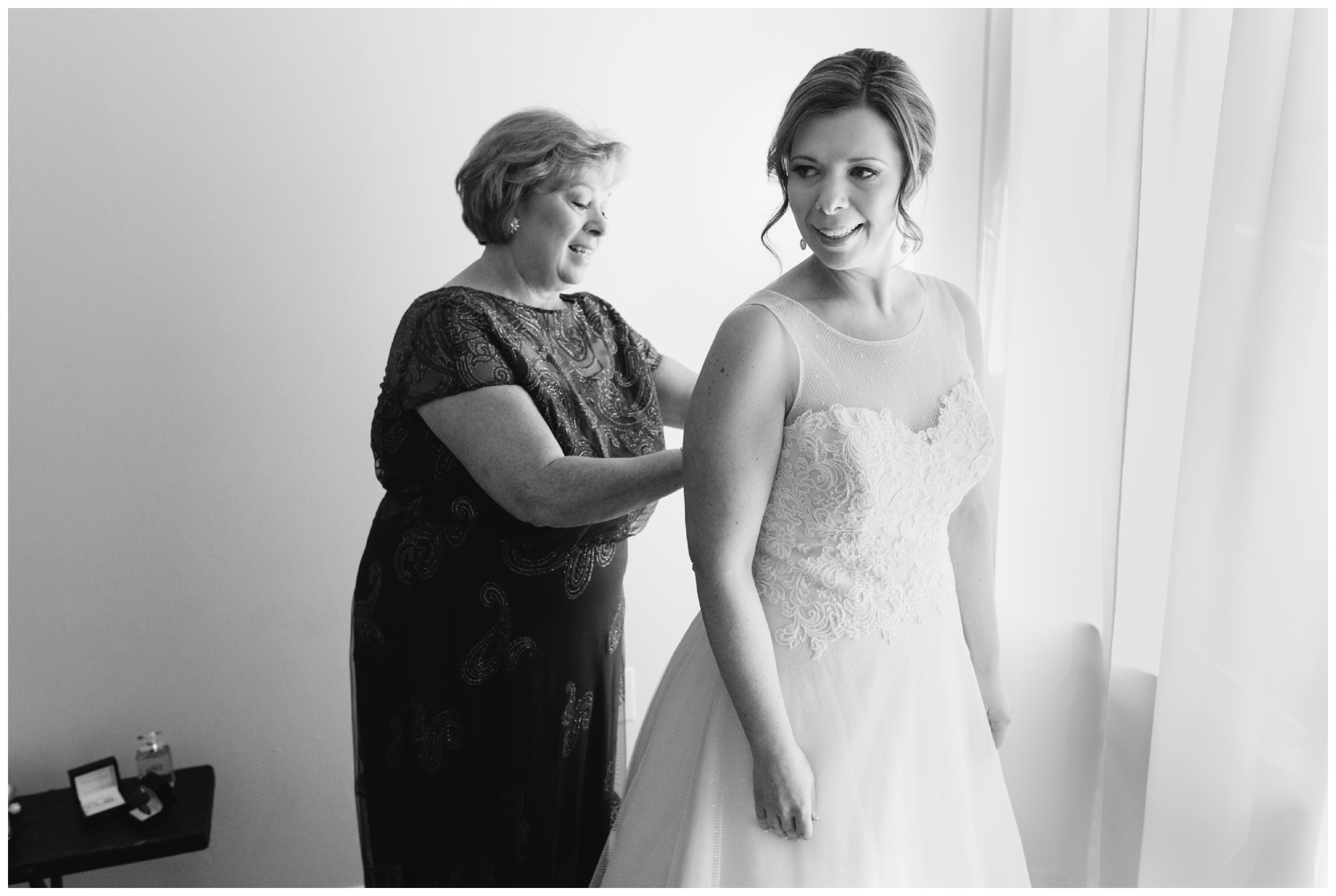 the bride's mother buttons up her dress using window light