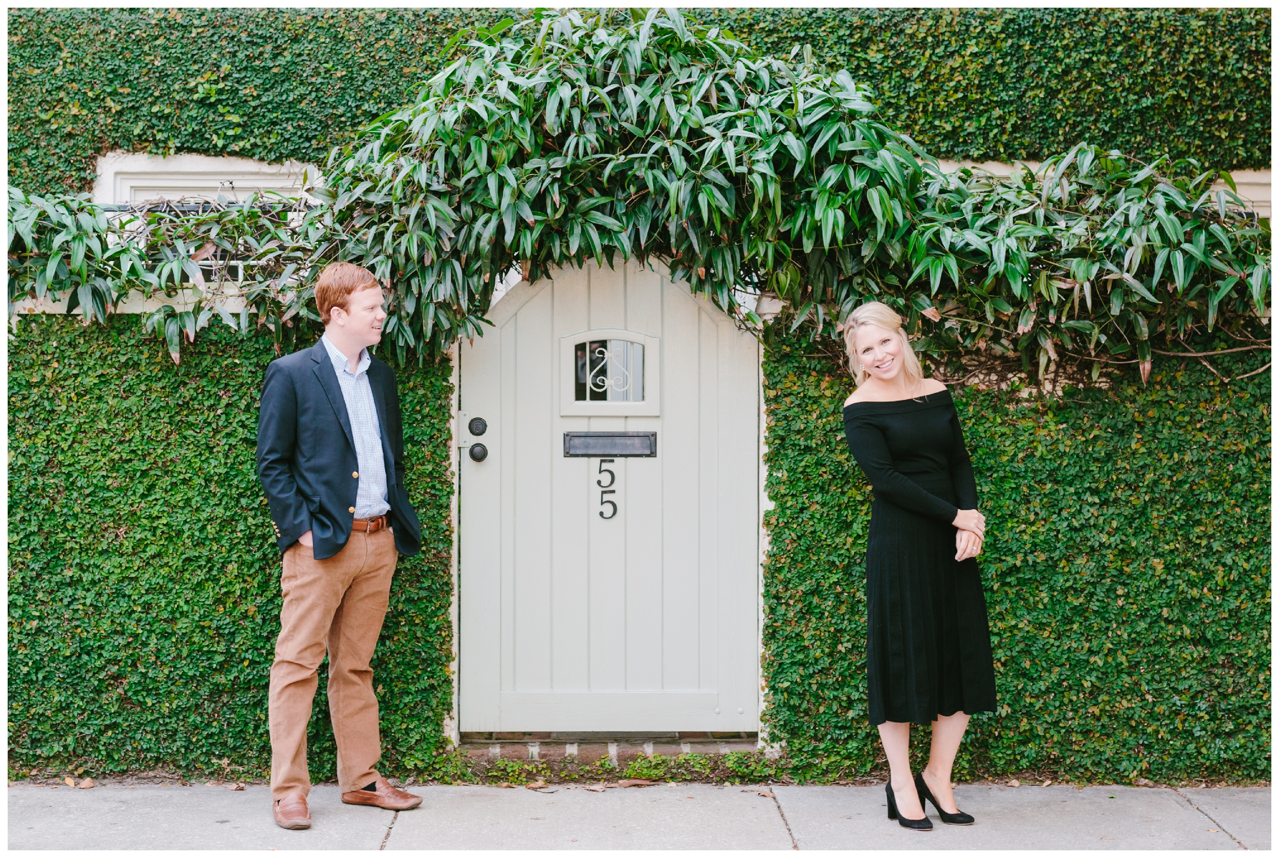 couple standing in front of a green wall