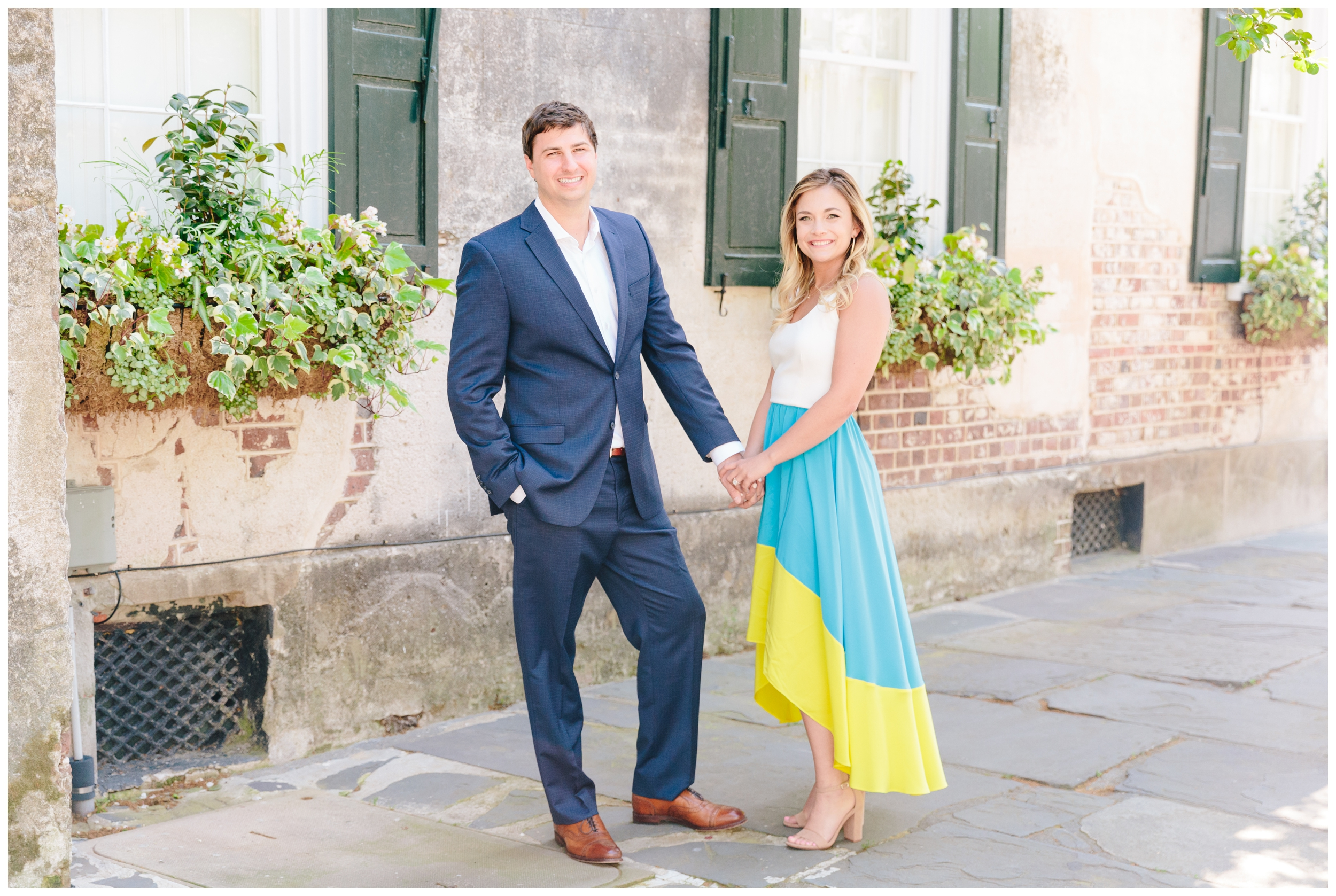 bride and groom holding hands in front of window boxes