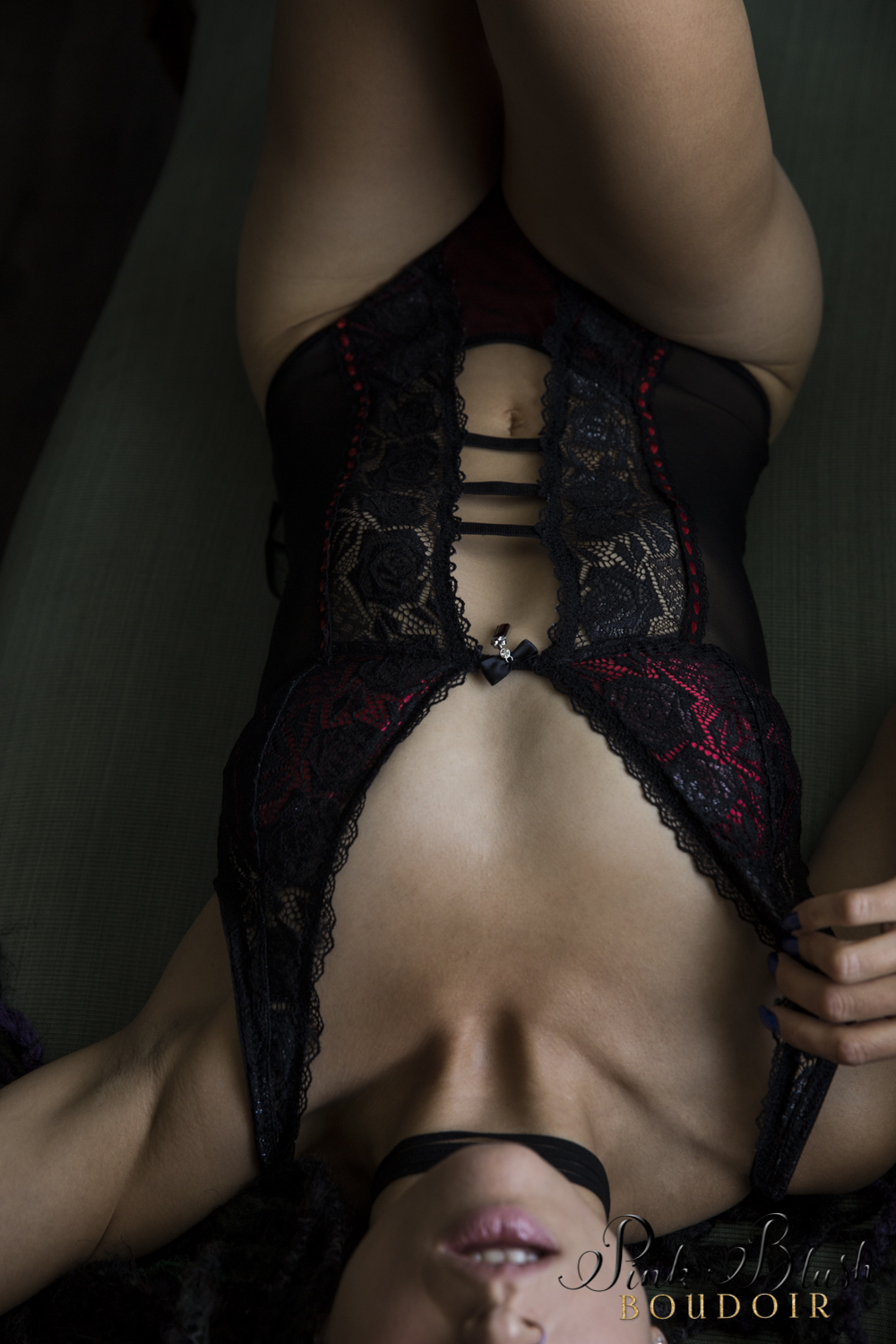 Boudoir Photography Edmonton, woman laying down in a black and red lace bodysuit
