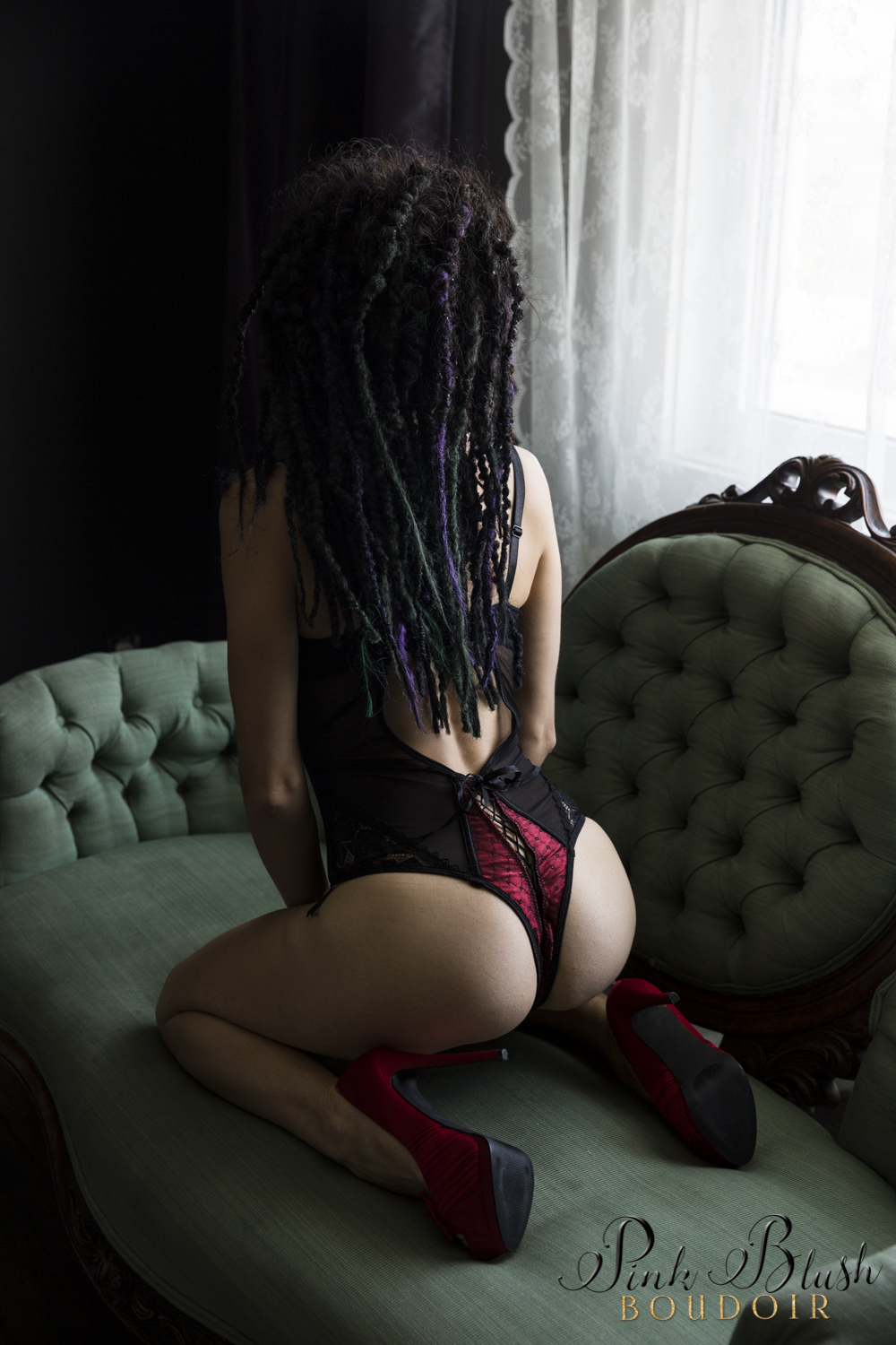Boudoir Photography Edmonton, a woman kneeling on her knees in a black and red bodysuit, butt showing