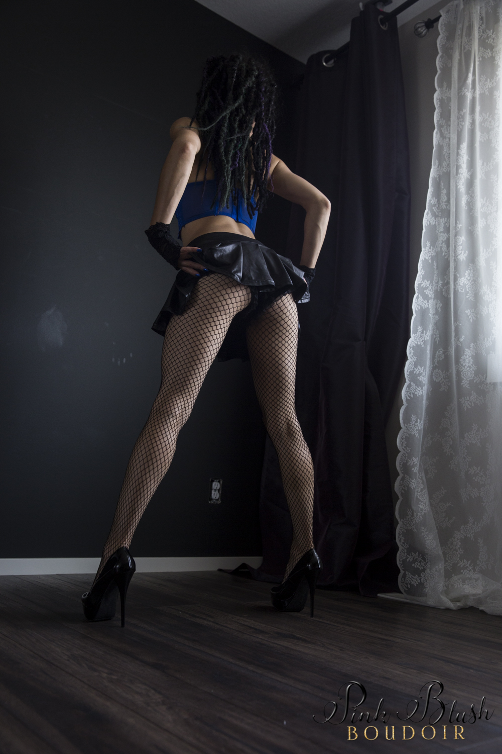 Boudoir Photography Edmonton, woman standing in a short skirt flipping it up to reveal her butt