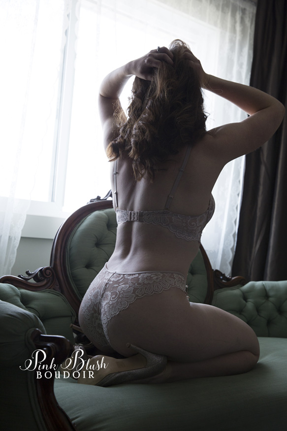 Edmonton Boudoir, a woman kneeling on her knees on a green couch