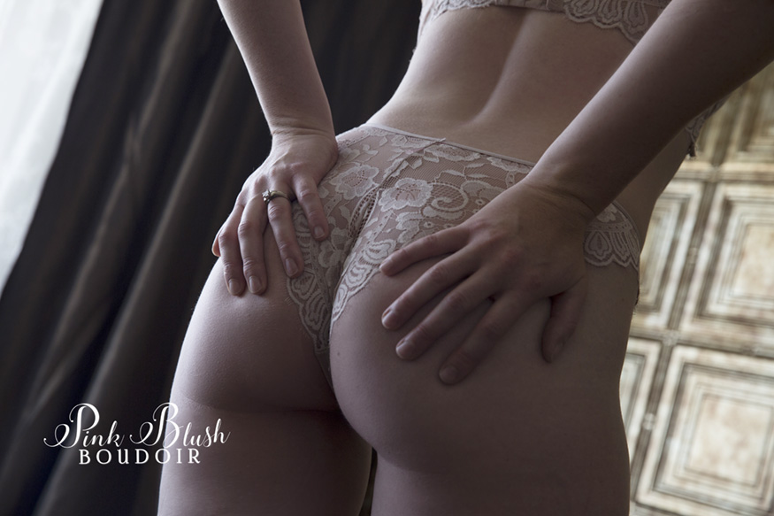 Edmonton Boudoir, nude panties a woman touching her butt in front of a gold wall
