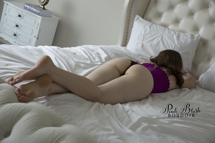 Edmonton Boudoir, a woman laying on her stomach wearing a purple corset