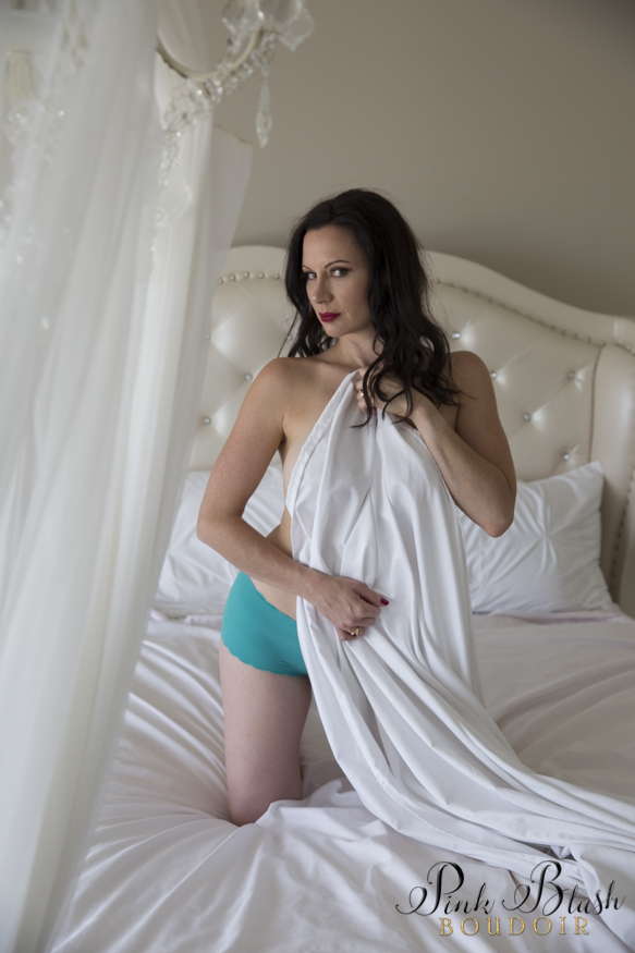 boudoir photos, a woman holding a white sheet against her kneeling on a white bed with aqua panties