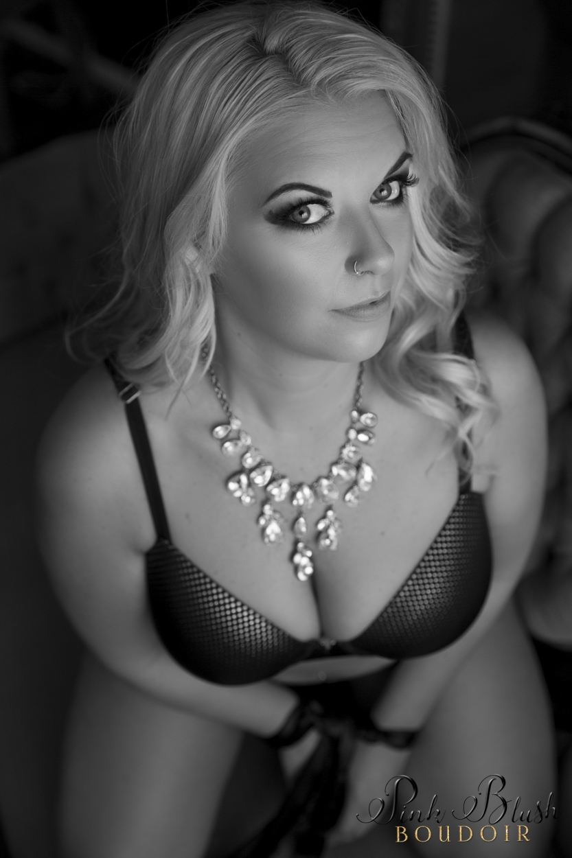 boudoir Edmonton, a woman looking at camera in a bra and panty set with her hands tied up