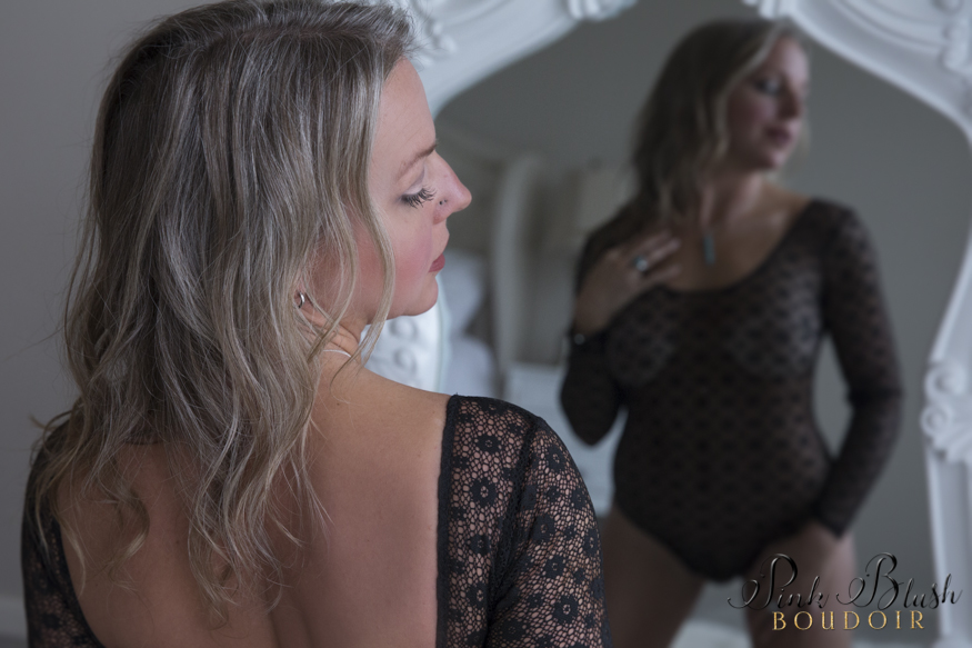 boudoir photos, a woman kneeling in front of a white mirror wearing a black lace body suit