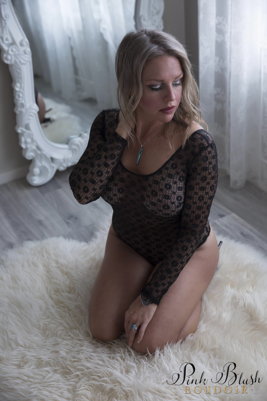 boudoir photos, a woman in a longsleeved lace body suit on a white rug