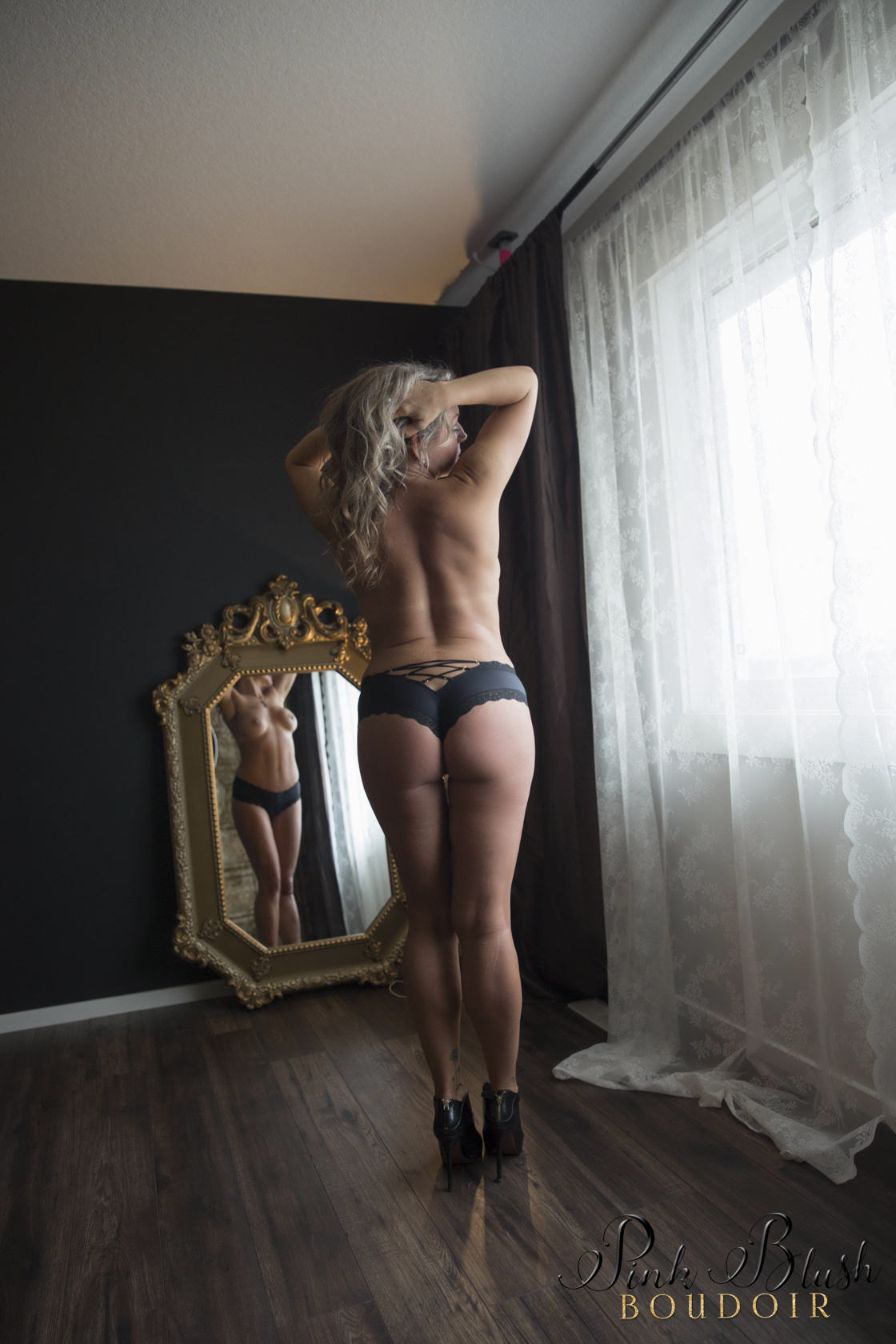 boudoir photos, a topless woman standing in front of a gold mirror