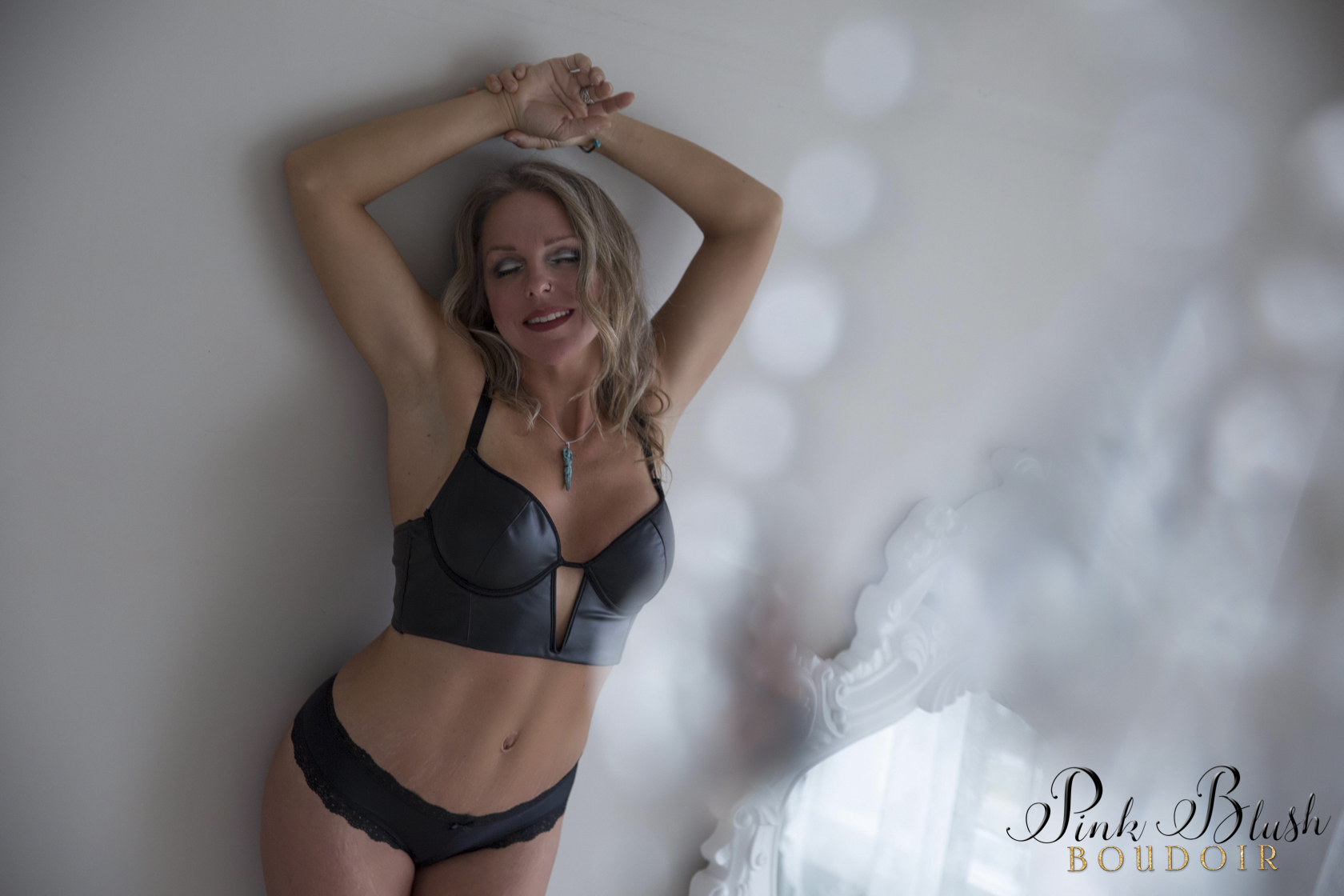 boudoir photos a woman in a black bra and panty set against a wall