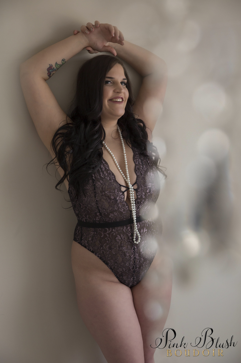 boudoir photography, a curvy woman in a lace teddy standing against a wall