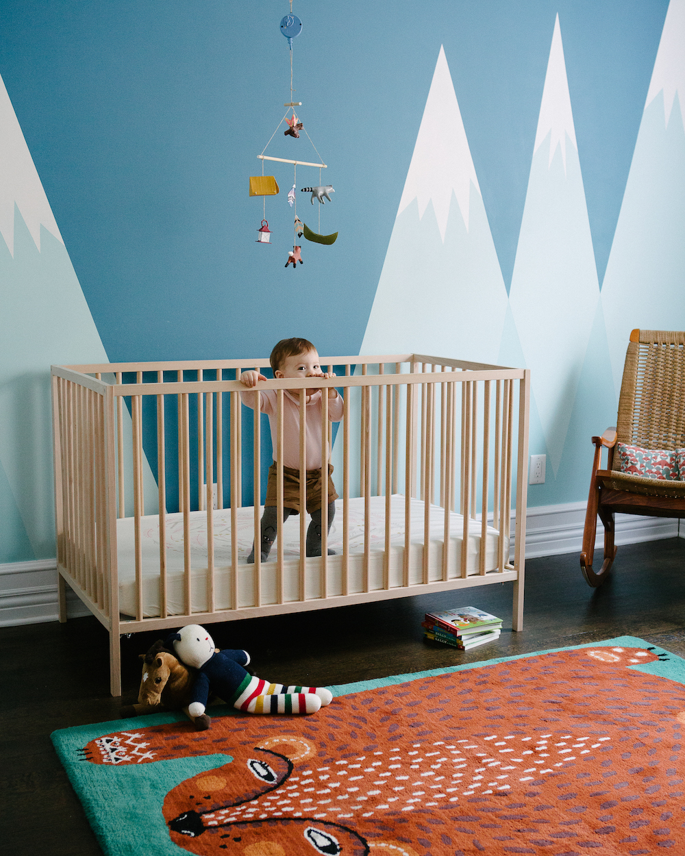 Happy murals, bright (but not too bright) colors, and whimsical rugs can create a safe and imaginative space for the kiddos. ( source )