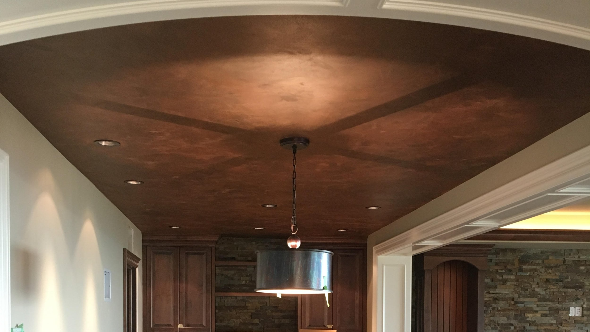 An aged copper finish that can combine mediums and textures such as leaf, paints, glazes, and plasters to create dimension and variation. Stunning on ceilings and decorative items like light fixtures and other accents to give the appearance of antique copper.