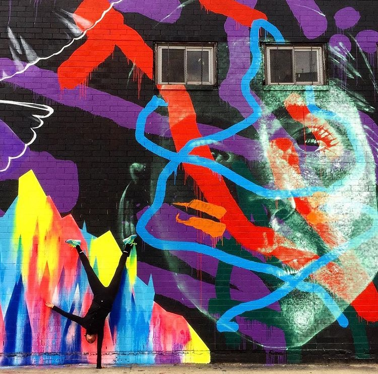 Check out our photo contest first place winner Cara Enright's dope shot in front of a mural by Askew1 and Vexta.
