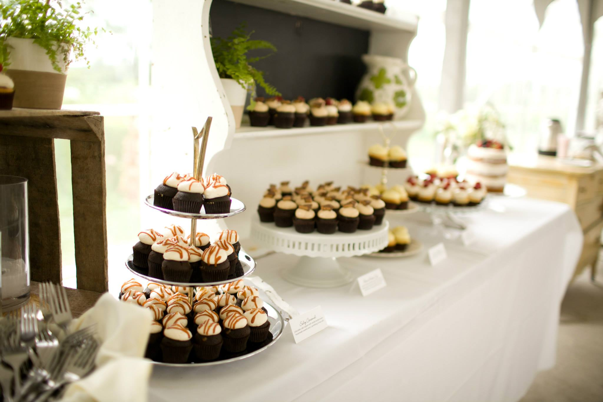 Mini Cupcakes on a buffet are always a crowdpleaser! The cupcakes on this table include Salty Caramel, Peanut Butter Cup, Lemon Drop and Vanilla Strawberry along with a Naked Cutting cake topped with fruit.
