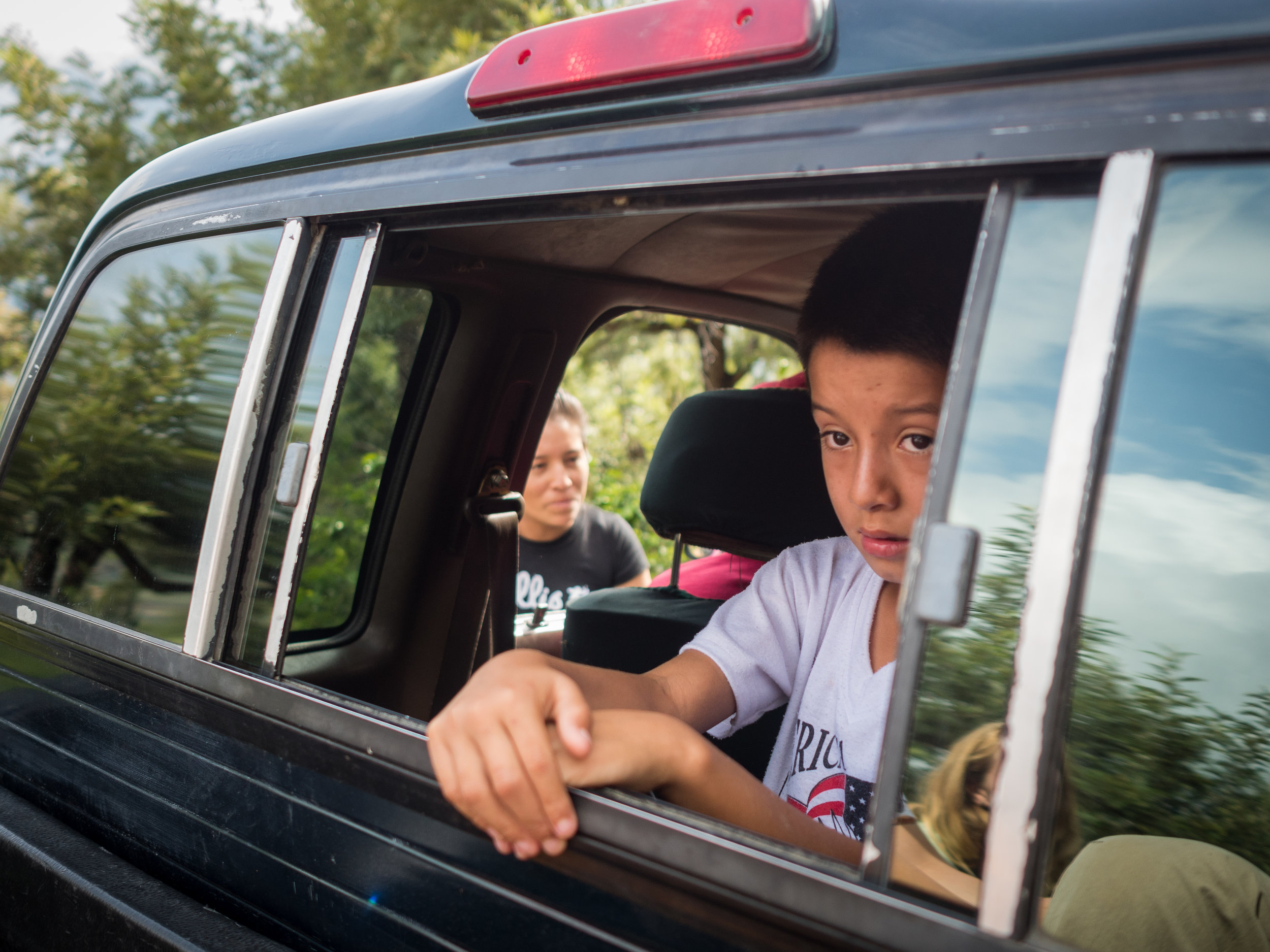 Cristian Aguilar Lopez looks out from the back of his fathers truck.