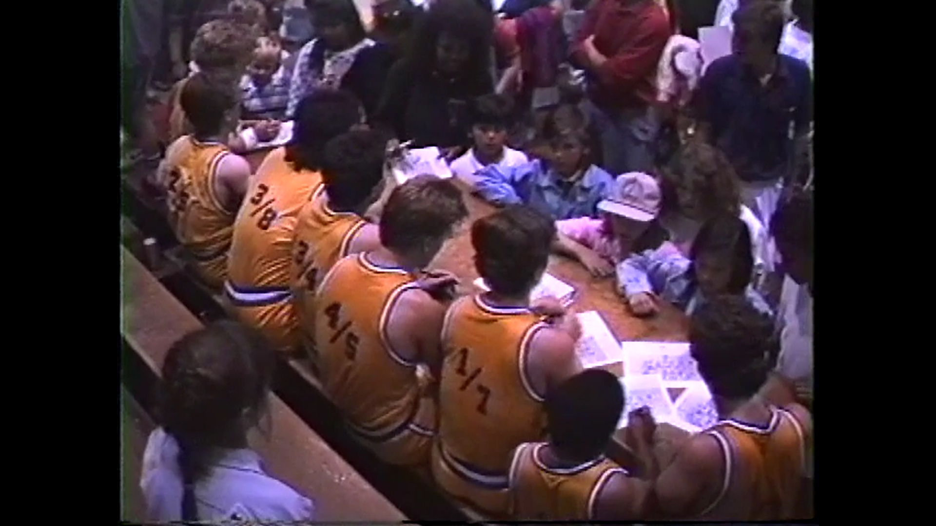 Members of The Hollywood Shorties sign autographs for stupefied children following a game versus the faculty of San Gabriel High School.