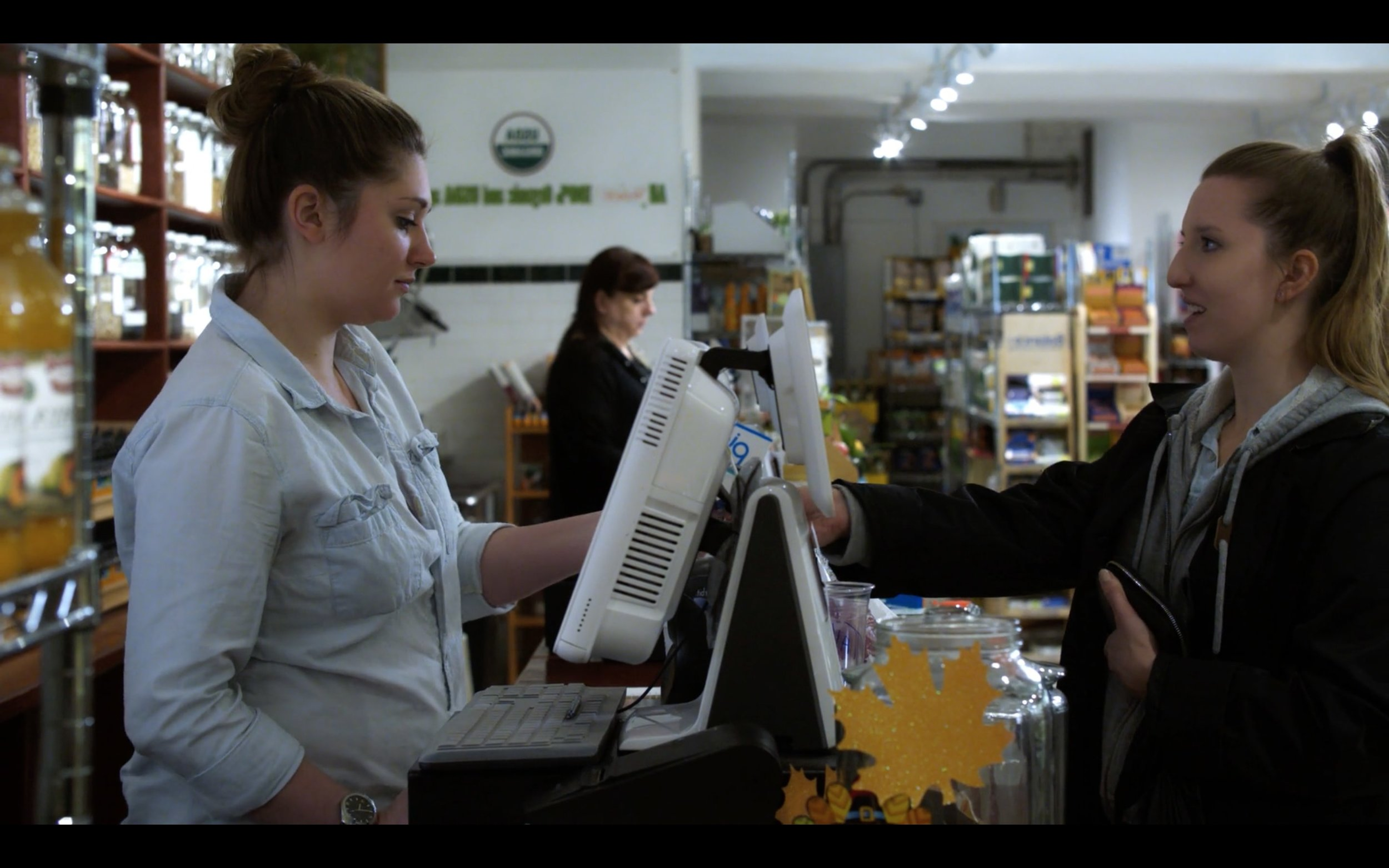 A rare moment of positive connection in our character's isolated New York City life. Cashier, Lindsey White. Young Woman, Katy Lueck. DP, Dina Graham