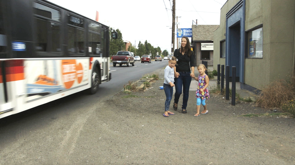 Kari:  Kari and her daughters huddled on street with no sidewalks as bus passes by.