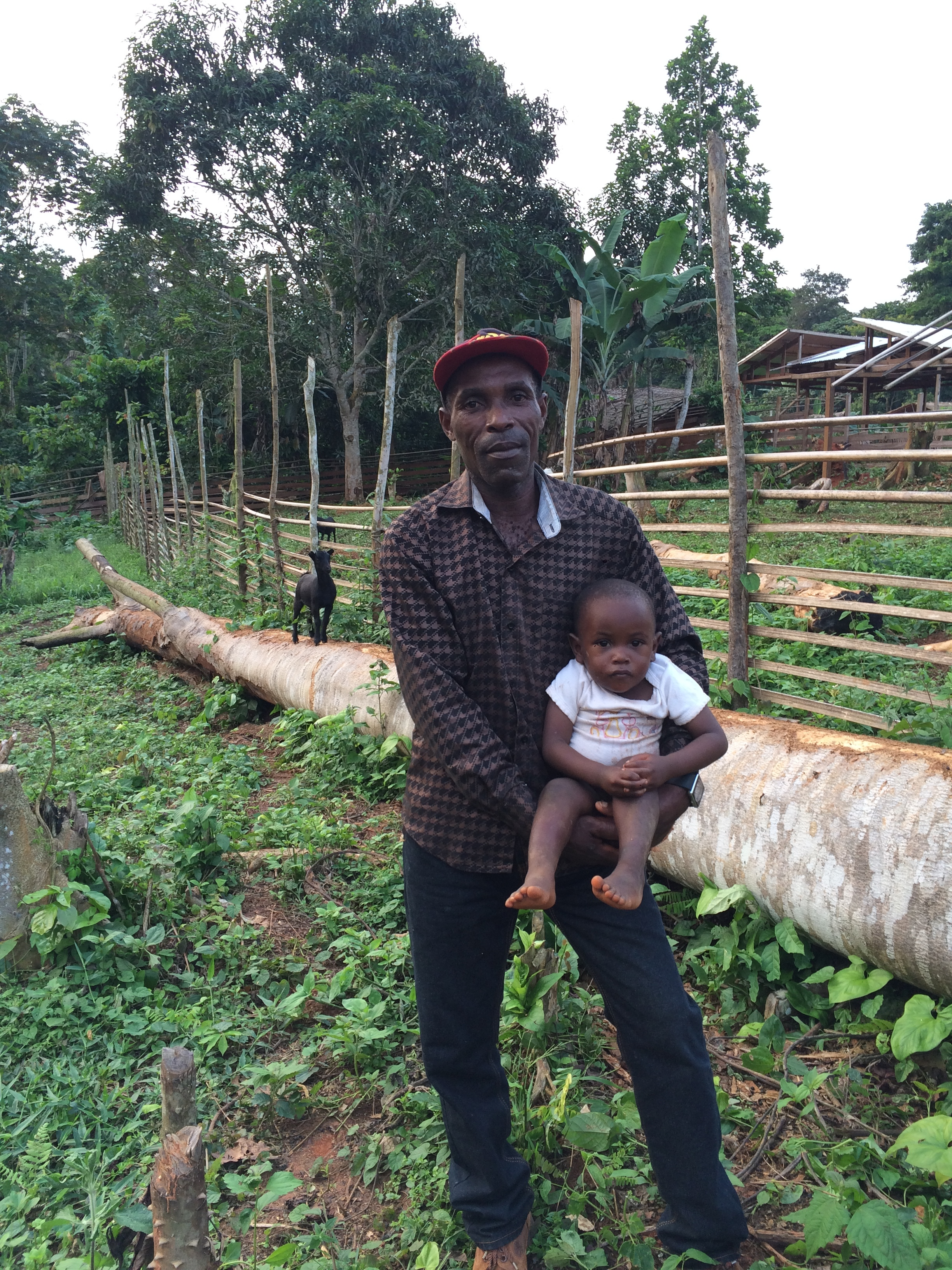 Silent Forests - Jean Paul, a former elephant poacher, now owns a cocoa farm and a small goat herd. He runs a support group for other reformed poachers in his area. He is pictured here with his youngest son.