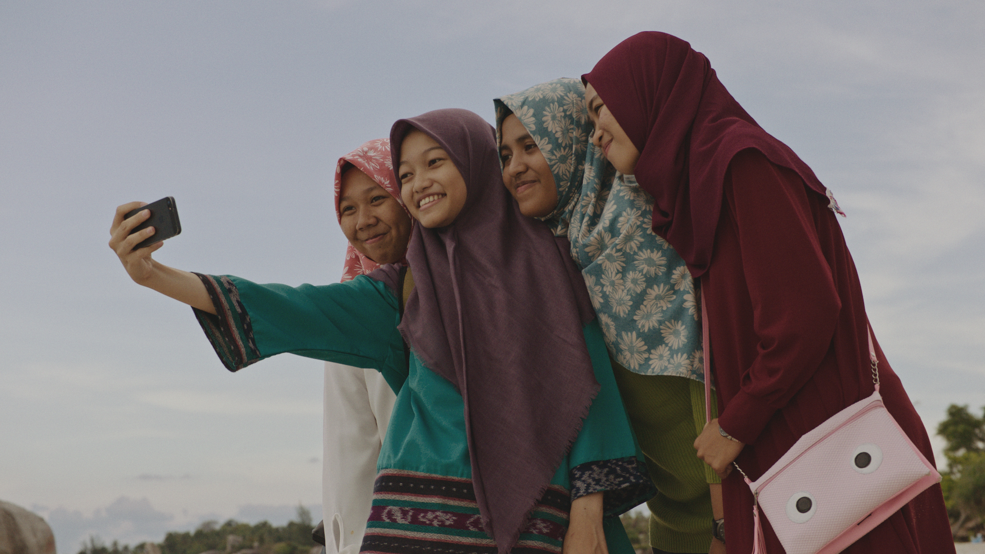Bottom: Nuha takes a selfie with friends