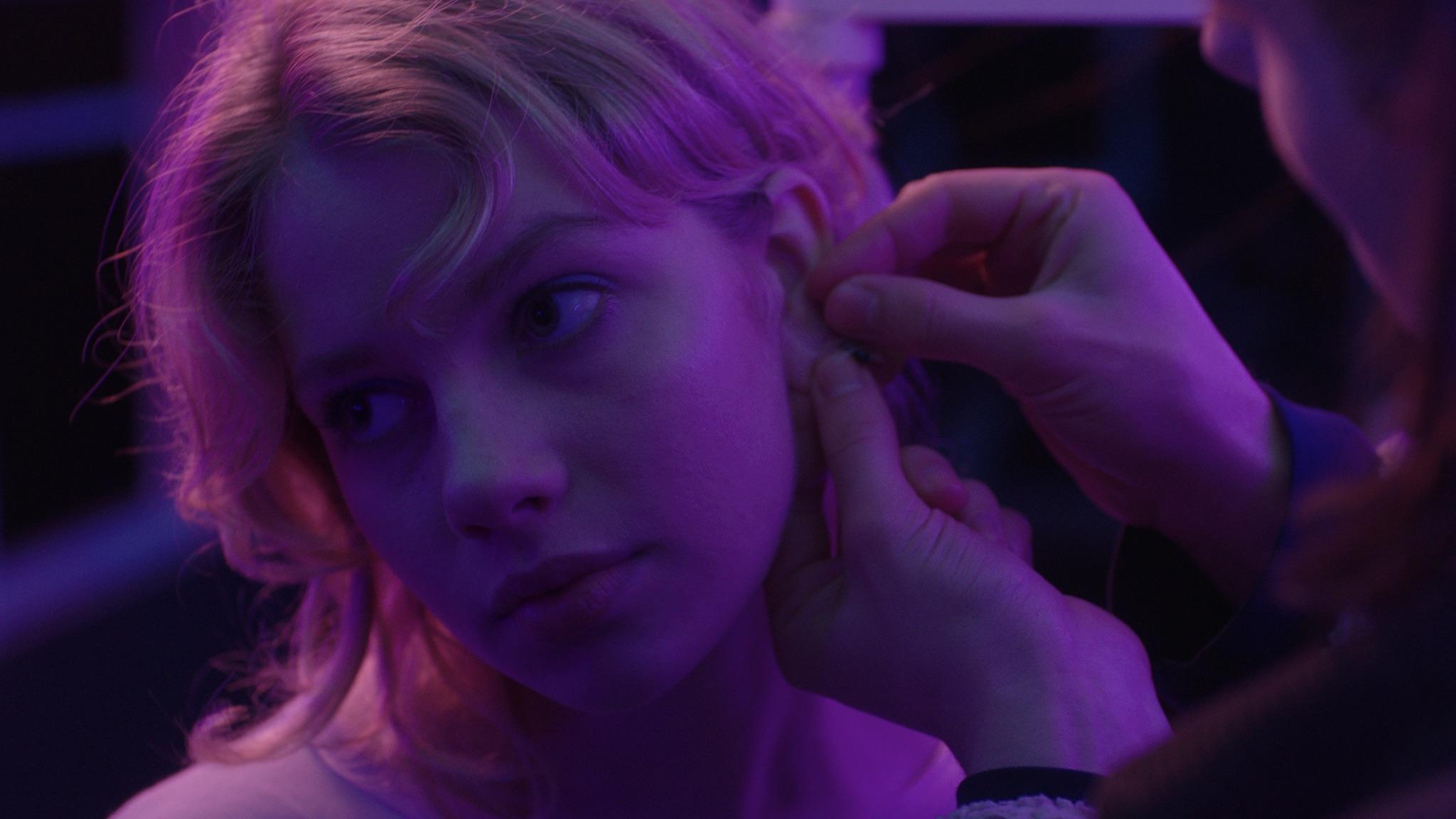 Charlie presses an earrings into Poppy's ear
