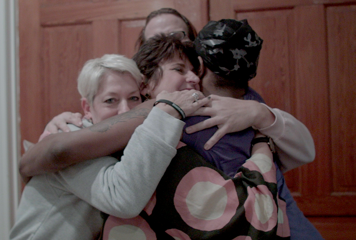 "Sara Cunningham, Susan Cottrell and Laura Taylor offer a group hug to a resident at Home for Hope, a shelter for LGBTQ people in Philadelphia during the first ""Free Mom Hugs Tour."""